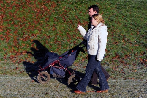 Couple walking in park with pushchair